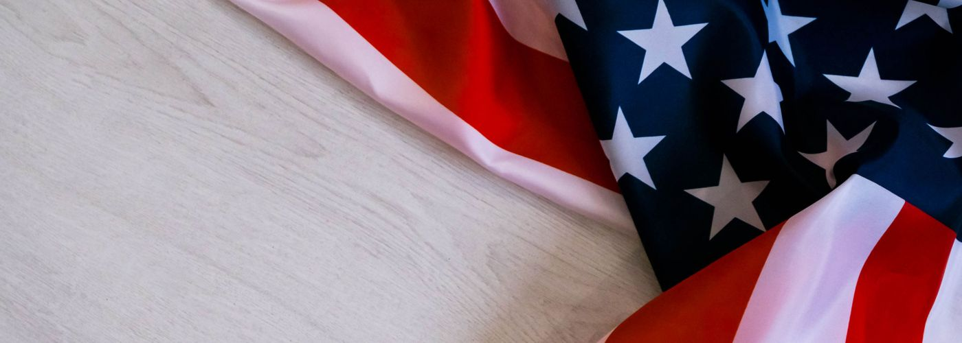 US flag on pale wooden background