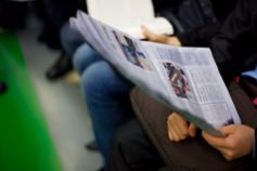 Person reading newspaper on train