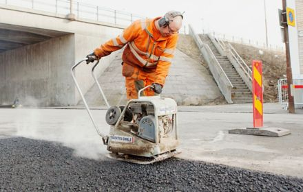 Worker laying an asphalt road