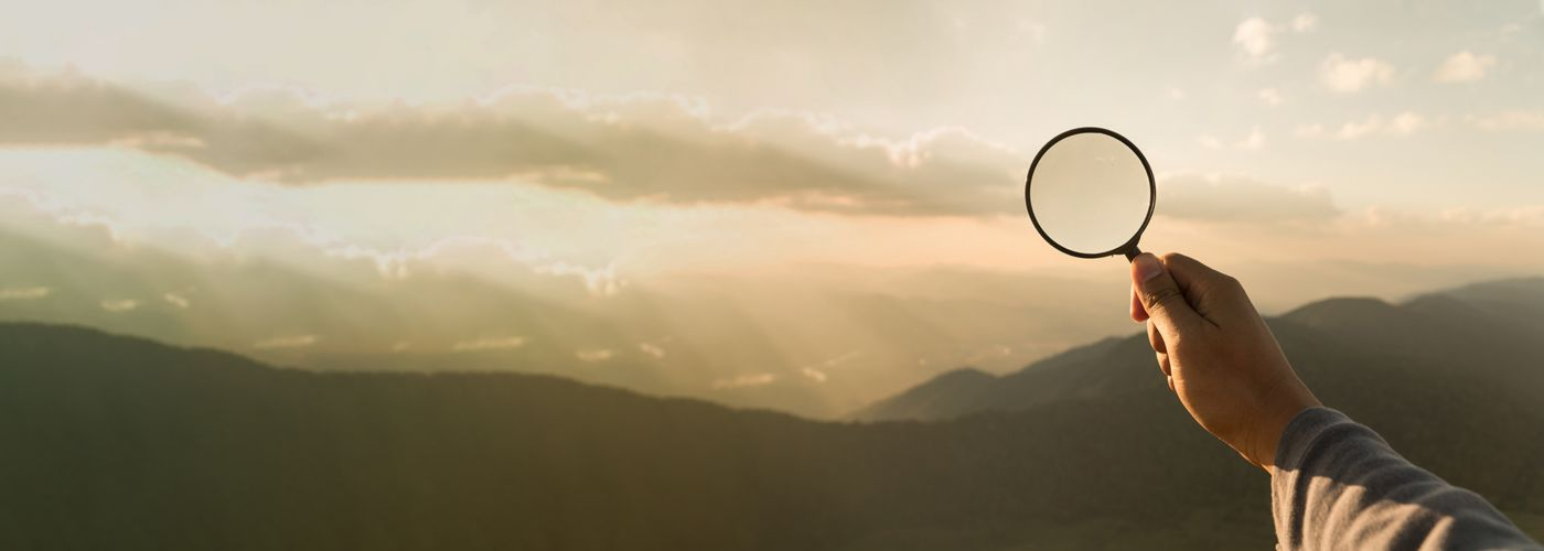 magnifying glass in front of sunset
