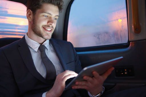 man in car holding tablet