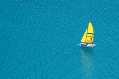 A boat with a yellow sail on the open water