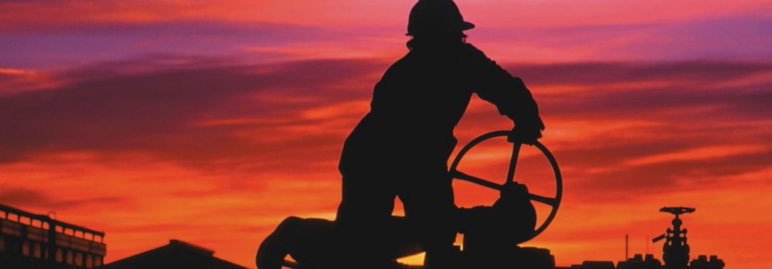 man turning oil gas valve at sunset