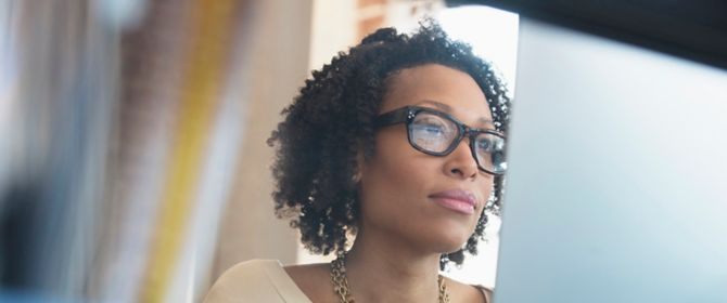 Woman with glasses looking at laptop.