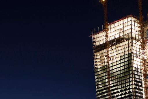 Building under construction lit up against the night sky