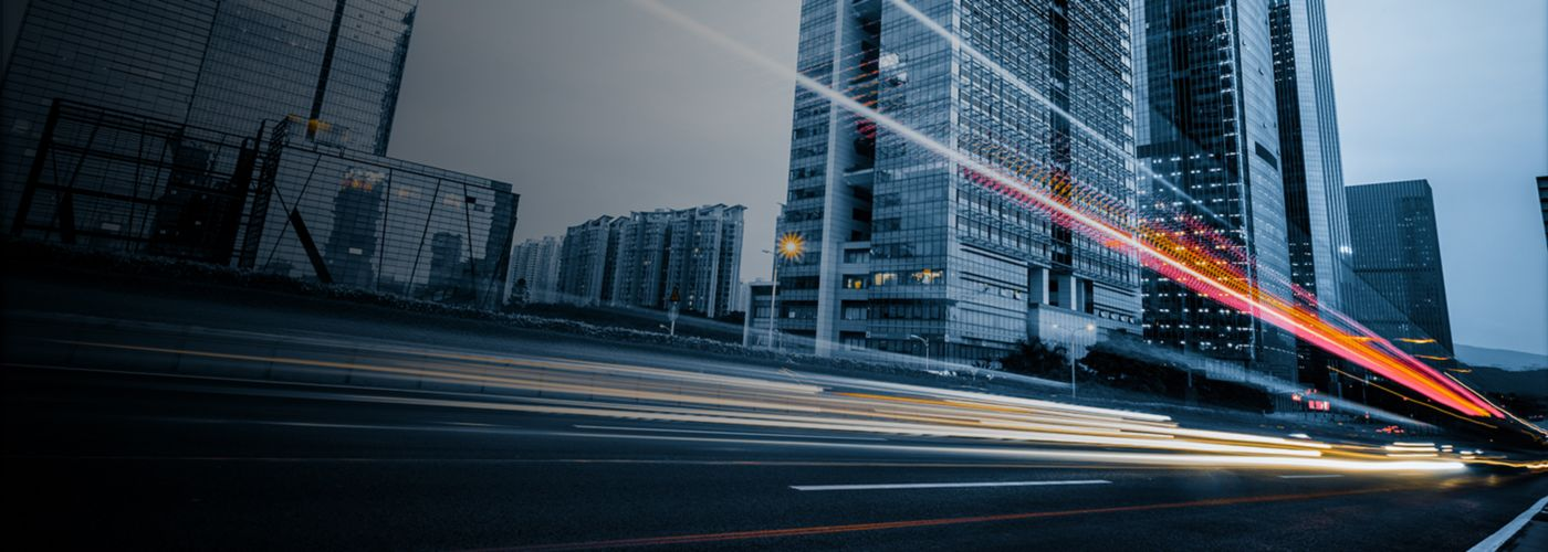 Long exposure of car's light trails on busy road besides huge glass buildings