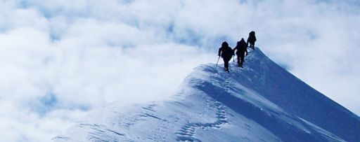Low angle view of hikers on snowy mountain
