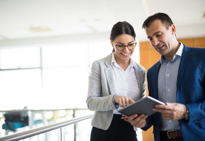 Man and woman discussing holding tablet blur background