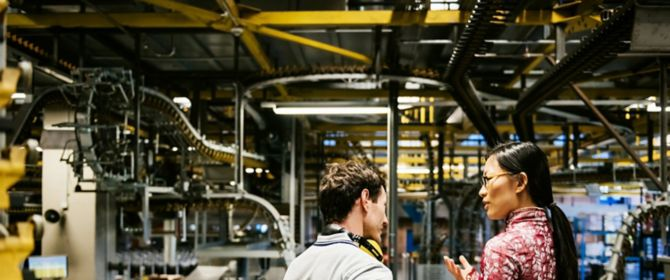 Man & woman in discussion against machines' background