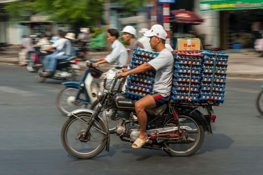 Man carrying egg cartons on a bicycle