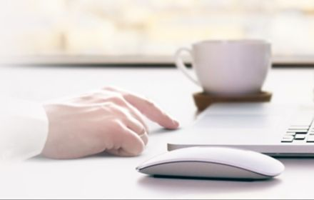Man hand on table with laptop glasses and blur background