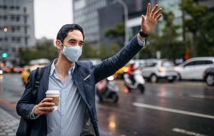 Man in mask waiving hand at taxi holding coffee