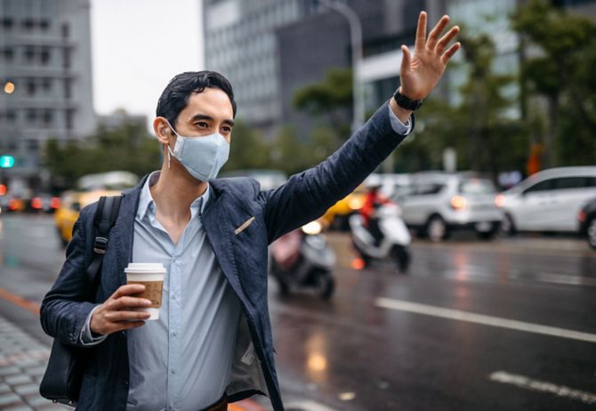 man in mask waiving hand at taxi