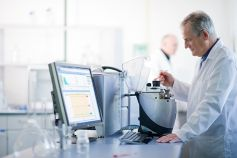 Man in a white coat working on a machine and computer