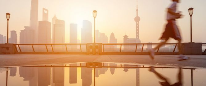 Man jogging in bright morning, city background