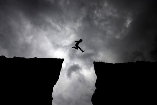 Man jumping from cliff - Dark clouds
