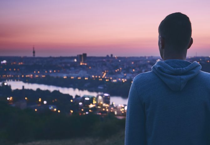 Man looking at city over a river at sunset