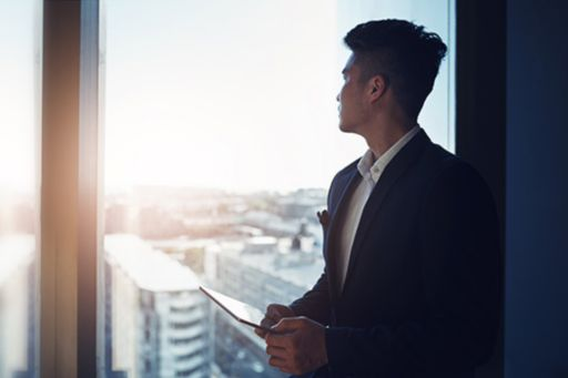 Compliance officer looking at the sun through his office window