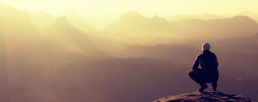 Man on a cliff edge looking out to misty valley