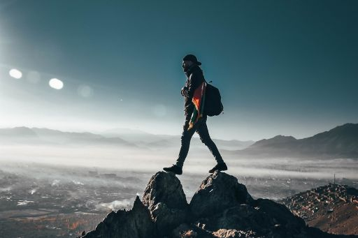 Adventurous man on hill top with bag-pack and clear sky