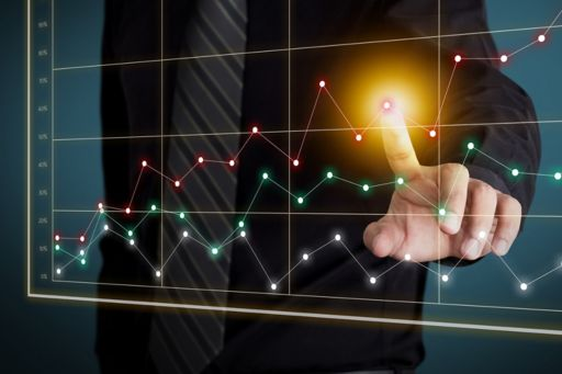 man pointing at dotted graph screen