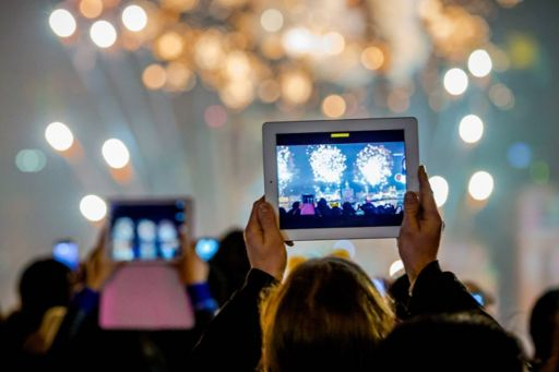 man recording a concert on his tablet