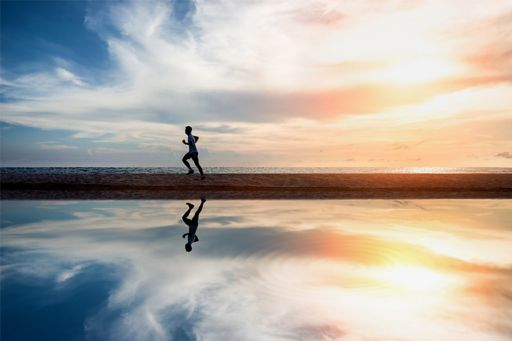 Man running on water shore under the red and blue sky