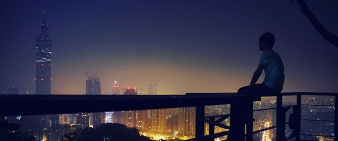 Man sitting on balcony railing and looking at city view