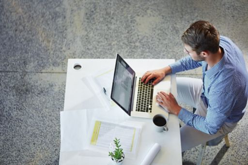 Man sitting on chair working on laptop