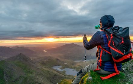 Man sitting on mountain watching horizon