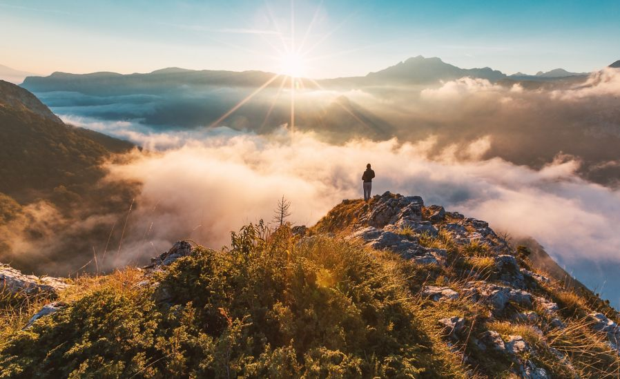 Man standing on mountain cliff above the clouds