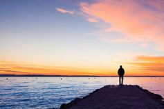 Man standing at river dock viewing evening red sky