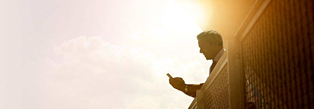 Man using cellphone, bright sunny day