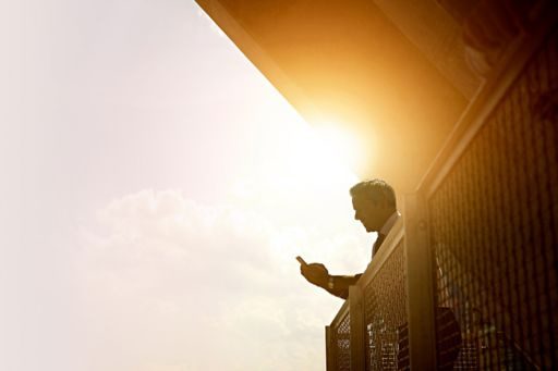 Businessman using cell phone on a bright sunny day