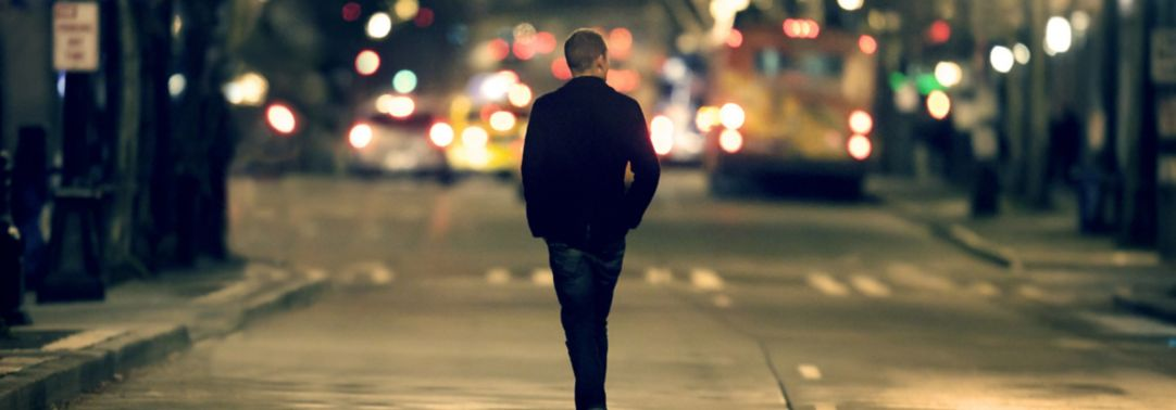 man walking down street at night
