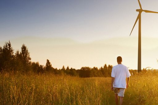 man-walking-through-field-with-windmill