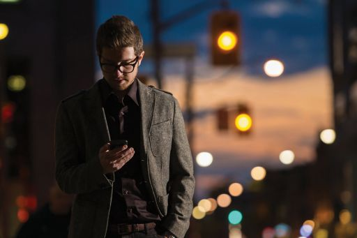 man wearing glasses using mobile