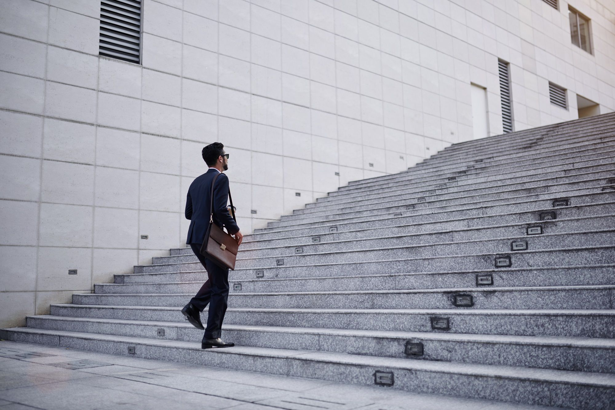 Man with bag walking up on the steps