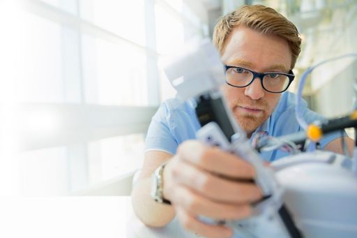 Man with brown hair wearing spectacles working in laboratory