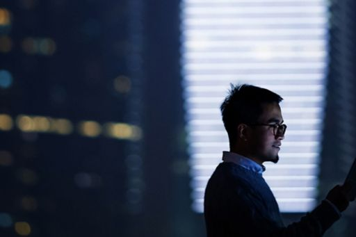 Man with glasses holding tablet in server room