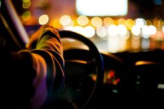 man with hand on steering wheel