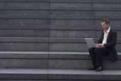 Man with laptop sitting on stairs