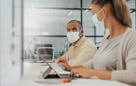 Man and woman sitting at office desk wearing face mask