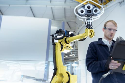 Man working in laboratory with robot arm and machines