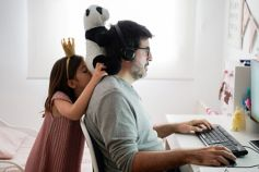 Man working on computer while his daughter is playing