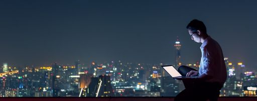 Man working on laptop with night lights in background