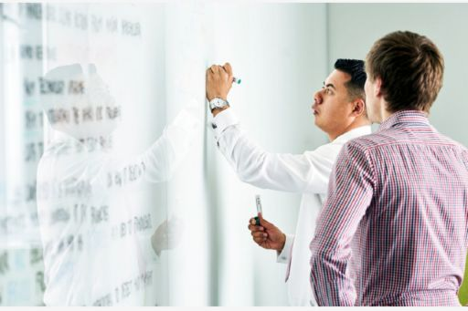 Businessmen writing on a white board