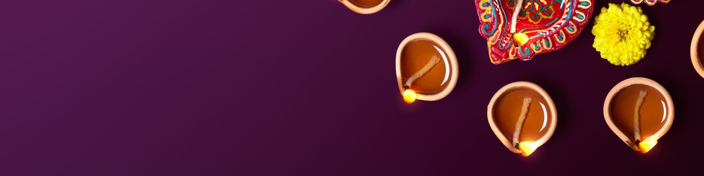 Many lit up diya and flowers against purple background