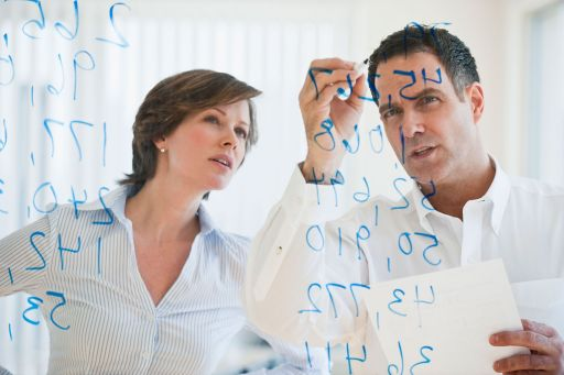 Businesswoman and businessman writing figures on glass