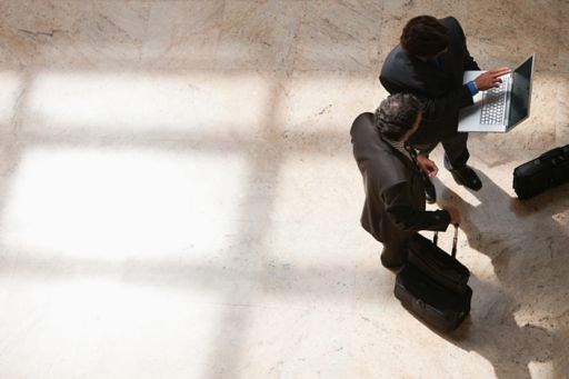 Top-down view of two businessmen looking at a laptop